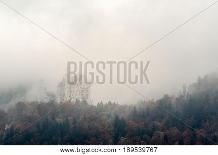 Fussen Bavaria Germany. Autumn view of Neuschwanstein Castle surrounded by yellow trees and fog.