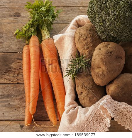 potatoes and carrots on wooden background close up