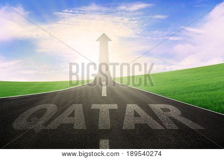 Empty road leading to an arrow upward and symbolizing success with a word of Qatar on the street