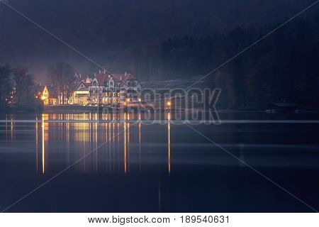 Hohenschwangau near Fussen in Bavaria Germany. Evening on the Alpsee lake surrounded by autumn forest and reflection of the evening city in the water.
