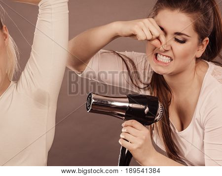Woman drying her female friend wet armpit using hair dryer. Getting rid of sweat and bad smell hyperhidrosis.