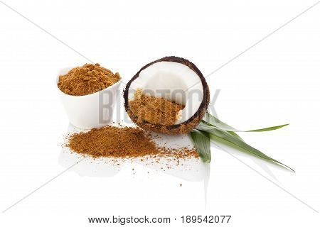 Coconut sugar background. Healthy sugar alternative. Coconut half palm leaves and brown coconut sugar isolated on white background.