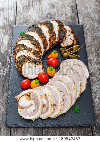 Slices of Homemade meatloaf veal and pork tenderloin stuffed with vegetables on black slate stone chalkboard on wooden background close up. Meat appetizer. Top view
