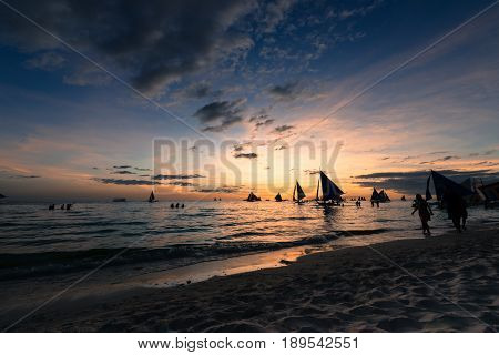 BORACAY, WESTERN VISAYAS, PHILIPPINES - MARCH 24, 2017: Tourists looking the sunset from the White Beach in Boracay