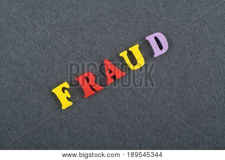 FRAUD word on black board background composed from colorful abc alphabet block wooden letters, copy space for ad text. Learning english concept
