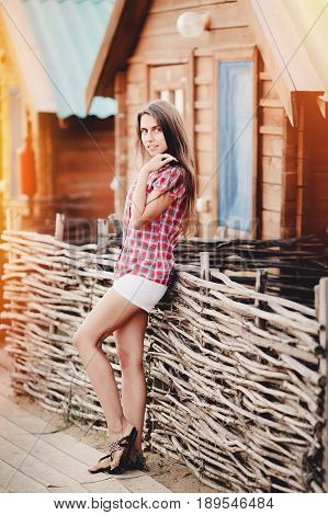 European young beautiful sunburnt girl stands near a wooden summer house and webbed fence. Conception is recreation on the landscape, campaign, camping, holidays, holidays at the seaside