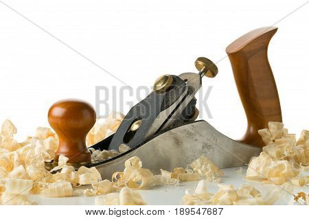 Woodworking hand planer tool on wooden boards in carpenter's workshop against white background with copy space