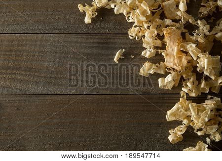 Light brown wood shavings from carpenter's hand planer or chisel work on wooden boards background with copy space