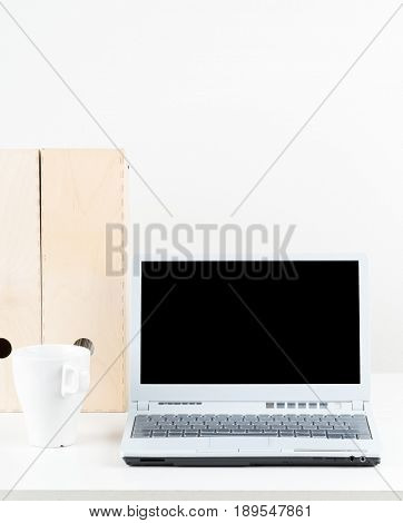 Office desk with cup folders and laptop with empty screen copy space