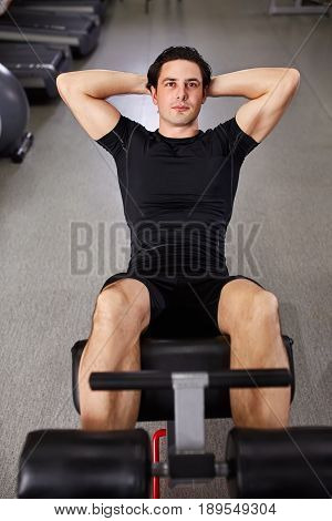 Young sportsman in black sportwear making abdominal exercises in gym. Portrait of the athletic man. Horizontal photo. Sportsman in the black t-shirt and shorts. Healthy lifestyle.