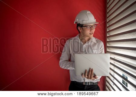 Young Asian Engineer or Architect dressed in white shirt and protective helmet working with laptop computer with red wall in background. Engineering Architecture and building construction concepts