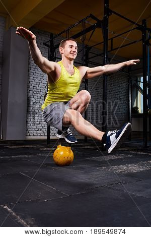 Young athletic man doing exercises in cross fit gym while crouching on one leg on the kettlebell. Sportsman in the sportwear, yellow t-shirt, shorts and sporty shoes. Portrait of smiling sportsman. Healthy lifestyle.