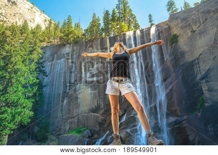 Hiking woman freedom in Yosemite National Park at Vernal Fall on Merced River from Mist Trail. Cheering happy hiker enjoying view of beautiful waterfalls. Summer travel holidays in California, USA.