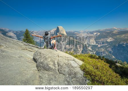 Hiking woman freedom in Glacier Point, Yosemite National Park. Cheering happy hiker enjoying view of popular Half Dome from Glacier Point overlook. Summer travel holidays concept. California, USA.