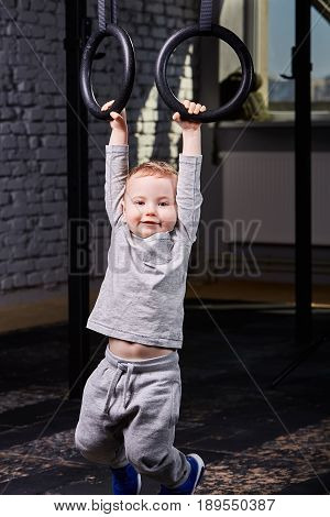 Little sporty boy in the grey sportwear hanging on gymnastic rings at gym. Portrait of smiling happy sporty child against brick wall. Vertical photo. Rearing child in the healthy lifestyle.