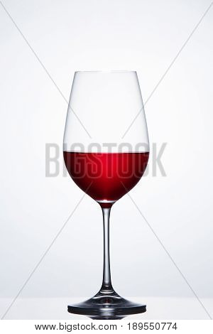 Red wine in the fragile pure wineglass standing against light bckground with reflection. Luxury lifestyle with relaxation. Elegant wineglass and clarity wine. Viticuclture, grapes and winery.