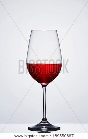 Halffull wine pure wine glass with red wine against light background with reflection. Clarity wineglass and wine. Luxury and relaxation. Viticulture, grapes and winery. Sommelier and tasting.