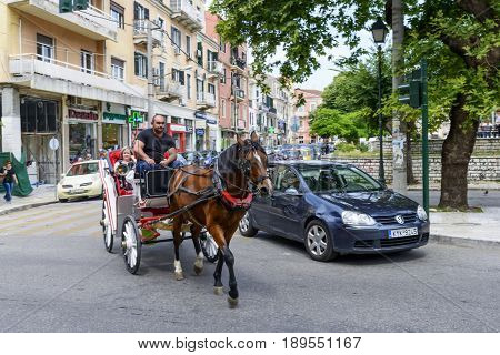 KERKYRA, GREECE - MAY 23: Tourists in a horse-drawn carriage on the old colorful street on May 23, 2017 in Kerkyra, Corfu island in Greece.