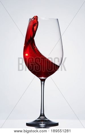 Splashing red wine in the elegant wineglass standing against light background with reflection. Concept of the luxury lifestyle and relaxation. Still-life and background. Sommelier and tasting.