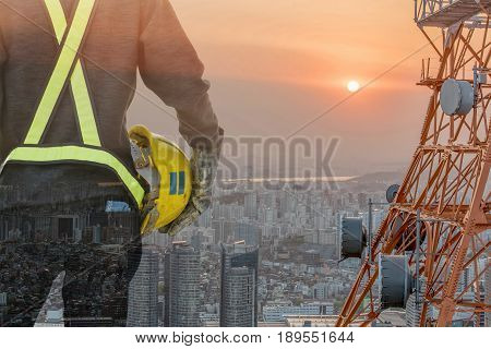 Double exposure businessman in suite with yellow safety helmet with telecommunication tower with blue sky background business industrial concept sunlight effect.