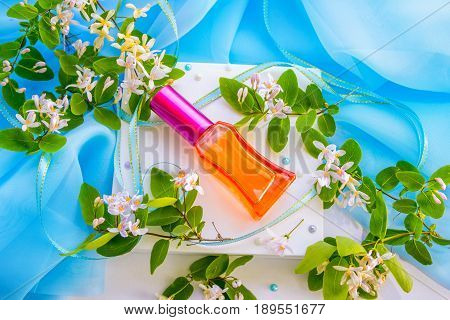 Red glass perfume bottle on a white box with barberry flowers, textile, ribbon and beads