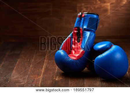 Two blue and red boxing gloves on brown wooden plank against wooden background. Concept of the sportive and active lifestyle. Background and still-life. Close-up and horizontal photo. Sportive exercixe and training. Sportwear and accessories.
