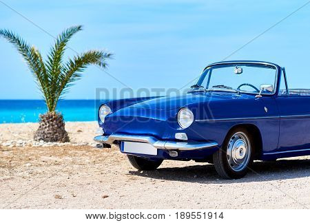 Retro cabriolet car on the beach near the turquoise sea. Idyllic scenery