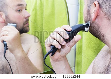 beauty hygiene shaving grooming and people concept - young man looking to mirror and shaving beard with trimmer or electric shaver at home bathroom