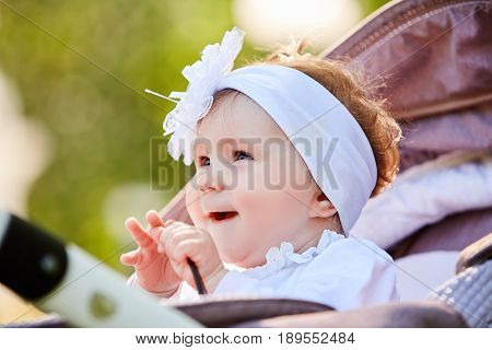 Portrait of the little baby girl sitting in a children's carriage in summer day. Cute baby girl in the white dress and with bow. Horizontal photo and close-up. Warm sunshiny day. Concept of the happy babies.