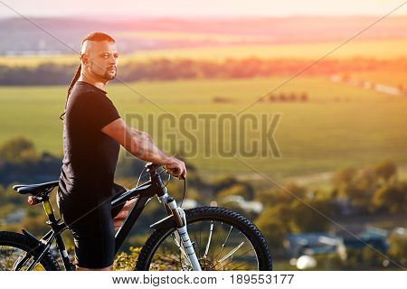 Close-up portrait of the mountain biker looking at beautiful landscape. Young cyclist in the black sportwear. Attractive man with mountain bicycle. Extreme travelling in the countryside in the summer season. Concept of the healthy lifestyle.