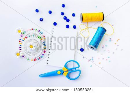 Sewing spools of blue and yellow caprone threads, blank spiral notepad, plastic scissors, glass beds and colorful pins on white background