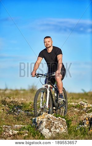 Young athlete cyclist riding mountain bike on the rocky trail in the countryside. Cyclist in the black sportwear and with sportive shoes. Beautiful landscape and blue sky with clouds. Summer season. Concept of the healthy and active lifestyle.