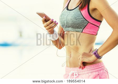 Attractive young woman on the beach after running listening to music on smartphone using earphones. Woman in sport outfit.
