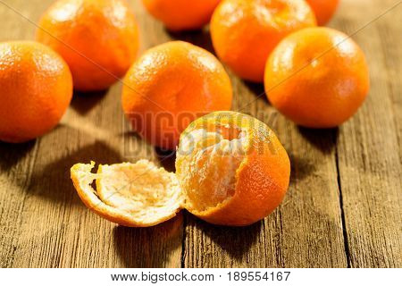 Orange tangerines on a wooden surface with one peeled