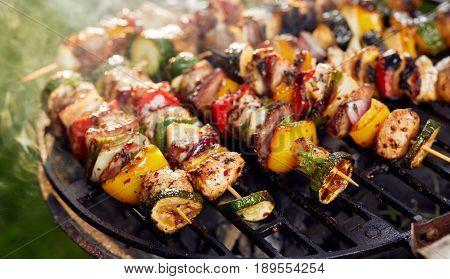 Grilled meat and vegetable skewers on a grilled plate, outdoor