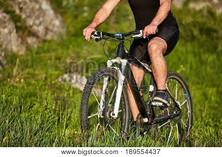 Close-up of the wheel of a bicycle and legs of the cyclist on the meadow. Detail of the sportsman and bicycle. Cyclist in the black sportwear and with sportive shoes. horizontal photo. Concept of the healthy lifestyle.