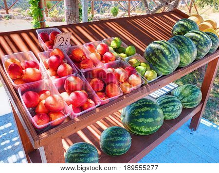 Classical road Greek stand rack shelf board table with colorful fruits peaches figs water melons for car traveling tourists on Greece Rodos island. Greece islands holidays vacation car travel tours