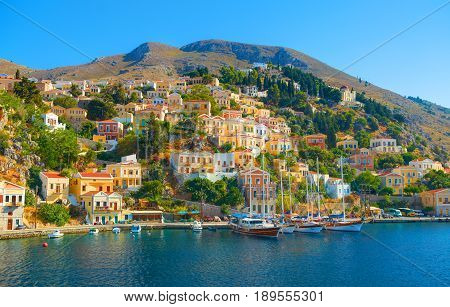 View on beautiful Greek sea port, classical ships yachts gingerbread houses on island hills, tourists, and blue sea bay Greece islands holidays vacation travel tours