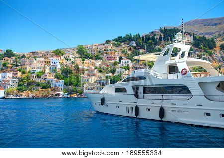 SIMI ISLAND, GREECE, JUNE 25, 2013: View on beautiful classic white yacht, Greek sea port, gingerbread houses on island hills, blue water bay. Greece islands white yachts vacations holidays tours