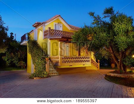 ZAKYNTHOS ISLAND, GREECE, MAY,30, 2016: Evening view on yellow classic Greek villa house cottage terrace Porto Gerakas villa in olive trees garden for tourists Evening highlighting. Holidays vacations