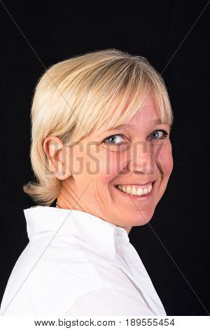 beautiful caucasian mature woman in white shirt, headshot - photograph on black background