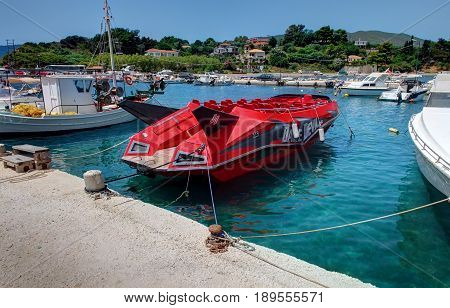 VASILIKOS, ZAKYNTHOS ISLAND, GREECE, JUNE 02, 2016: Red speed boat Dake Devil jet for tourists. Agressive design boat. Greece islands holidays trips to Blue caves. Sport car style Ferrari boat