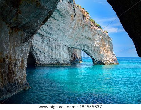 Blue caves rock arces arches of Blue caves from sightseeing boat with tourists in blue water of Ionian Sea inside cave, Island Zakynthos, Greece holidays vacation tour. Trip from Agios Nikolaos port