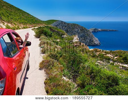 ZAKYNTHOS ISLAND, GREECE, JUN,06, 2016: Beautiful perspective view on red car on road with pretty girl, Ag. Ioannis island in Ionian Sea. Famous sightseeing car travel. Greece holidays vacations tours