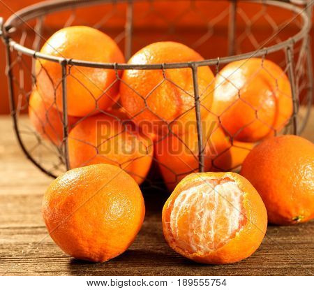 Orange tangerines on a wooden surface and in a basket