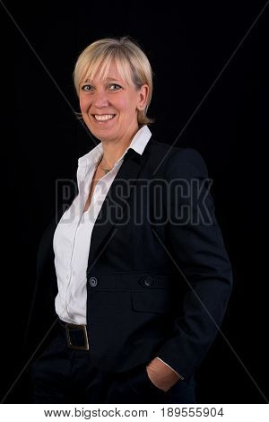 successful and beautiful european mature woman in business dress, side view - photograph on black background