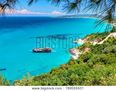 Beautiful view on amazing island bay with pirate corsair style boat ship, swimming people, beach in Ionian Sea blue water, Greece islands holidays, close to Xigia sand beach on Zakynthos Greek island