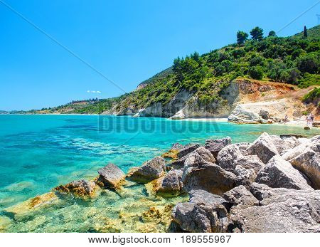 Beautiful view on Zakynthos stone and sand beach, stone rocks, swimming and toasting people on the beach, blue ultramarine water of Ionian Sea, reefs, near to Xigia stone beach Greece islands holidays