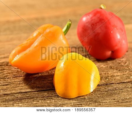 Assortment of colorful bell peppers on a wooden surface