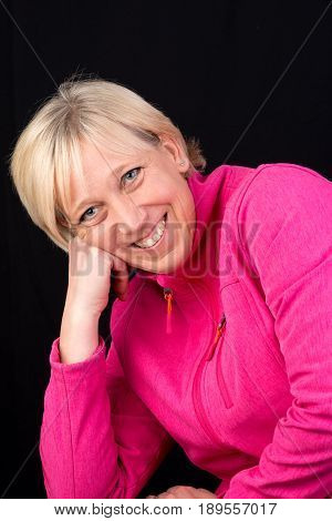Beautiful european mature woman in pink soft shell portrait - photograph on black background